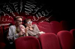 Cute couple in cinema watching movie stock images