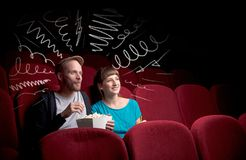 Cute couple in cinema watching movie. Young cute couple sitting in cinema, and eating popcorn while watching movie with doodle graphics stock images