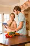 Cute couple cooking and using tablet Royalty Free Stock Photos