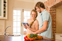 Cute couple cooking and using tablet Stock Photography