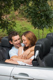 Cute couple cuddling in the backseat and chatting Stock Image
