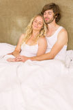 Cute couple cuddling in bed. In the bedroom stock photo