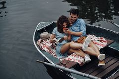 Cute couple. Handsome young men feeding his girlfriend with an apple while sitting in the boat royalty free stock photos
