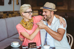 Cute couple on a date giving each other food. At the cafe Stock Images