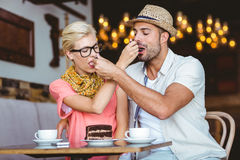 Cute couple on a date giving each other food. At the cafe Stock Image