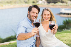 Cute couple on date handing red wine glasses Stock Image