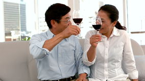 Cute couple on date holding red wine glasses. At home stock video footage
