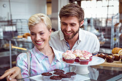 Cute couple on a date pointing chocolate cakes Royalty Free Stock Images