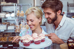 Cute couple on a date pointing chocolate cakes Stock Photo