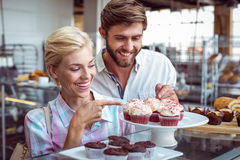 Cute couple on a date pointing chocolate cakes Stock Photos