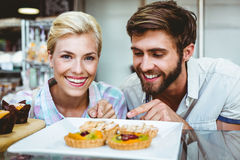 Cute couple on a date pointing fruit pie. At the bakery stock photos