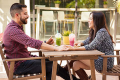 Cute couple on a date. Profile view of a young couple holding hands during a lunch date and having fun Stock Photography