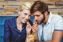 Cute couple on a date sharing a glass of orange juice Stock Images
