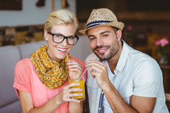 Cute couple on a date sharing an orange juice Royalty Free Stock Images