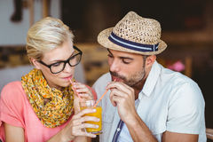 Cute couple on a date sharing an orange juice Stock Image