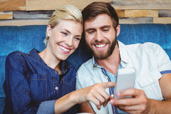 Cute couple on a date watching photos on a smartphone Stock Images