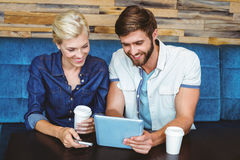 Cute couple on a date watching photos on a tablet Royalty Free Stock Photo