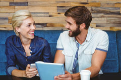 Cute couple on a date watching photos on a tablet stock photo