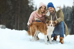 Cute couple with dog near forest. Winter vacation royalty free stock images