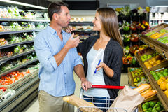 Cute couple doing grocery shopping together Stock Photo