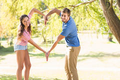 Cute couple doing heart shape with their hands Stock Photo