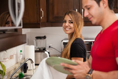 Cute couple doing some chores. Gorgeous young women and her boyfriend doing some house chores together royalty free stock images