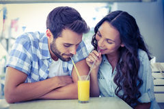 Cute couple drinking an orange juice together Royalty Free Stock Images