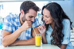 Cute couple drinking an orange juice together Stock Photo