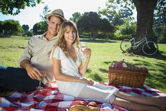 Cute couple drinking white wine on a picnic smiling at camera Stock Images