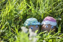 Cute couple of Easter eggs with smiling faces. In spring sunlight of green grass Royalty Free Stock Photos