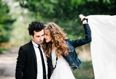Cute couple embraces. Portrait of stylish young man in suit with tie hugs beautiful girl holding white dress in air. Concept of stock images
