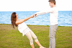 Cute Couple Enjoying Themselves By the Beach. Portrait of a cute young couple enjoying themselves by the beach Stock Photo