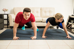 Cute couple exercising together at home Royalty Free Stock Images