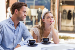 Cute couple facing relation difficulties. On a cafe terrace royalty free stock photo