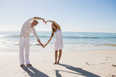 Cute couple forming heart shape with arms Stock Image