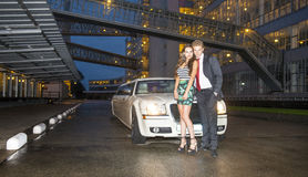 Cute couple in front of a limousine Stock Photo