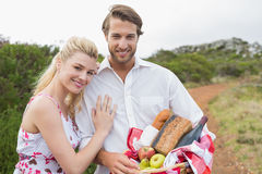 Cute couple going for a picnic smiling at camera Stock Image