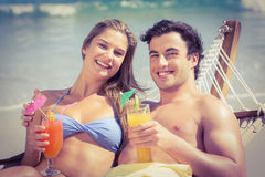 Cute couple in the hammock drinking a cocktail Stock Image