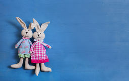 Cute couple of handmade sewed easter bunny on blue wooden background Royalty Free Stock Photo
