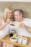 Cute couple having breakfast in bed. In their room Stock Photography