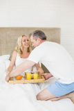 Cute couple having breakfast in bed Stock Photos