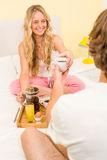 Cute couple having breakfast sitting on their bed Royalty Free Stock Photography