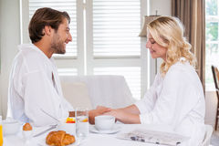 Cute couple having breakfast in their bathrobes Royalty Free Stock Image