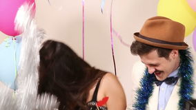 Cute couple having fun in party photo booth. Cute young couple having fun in party photo booth stock video footage