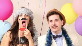 Cute couple having fun in party photo booth. Cute young couple having fun in party photo booth stock footage