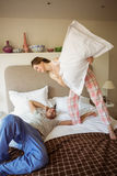 Cute couple having a pillow fight Royalty Free Stock Photos