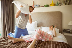 Cute couple having a pillow fight. At home in the bedroom stock photos