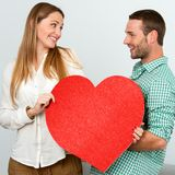 Cute couple holding big red heart sign. Stock Images