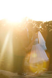 Cute couple is holding hands and kissing on the background sunse Royalty Free Stock Photo
