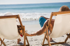 Cute couple holding hands while lying on their deck chairs stock photos